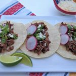 3 tacos on a white plate with lime wedges