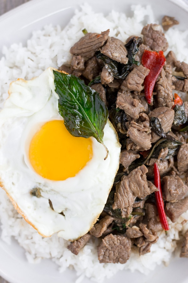 Thai Beef Basil on a white plate with rice and a fried egg on the side.