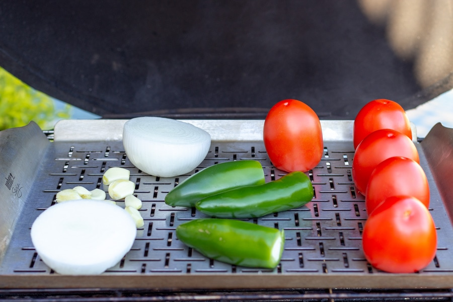 Tomatoes, jalapenos, onions, and garlic on a grill grate for roasting.