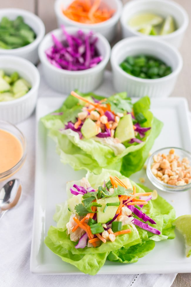 2 lettuce wraps on a plate with toppings in small bowls.