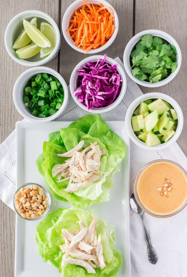 Overhead view of lettuce wraps with topping in individual cups.