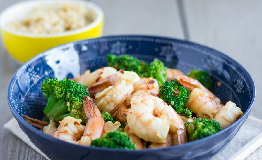 Landscape view of shrimp and broccoli stir fry with a small yellow bowl in the back.