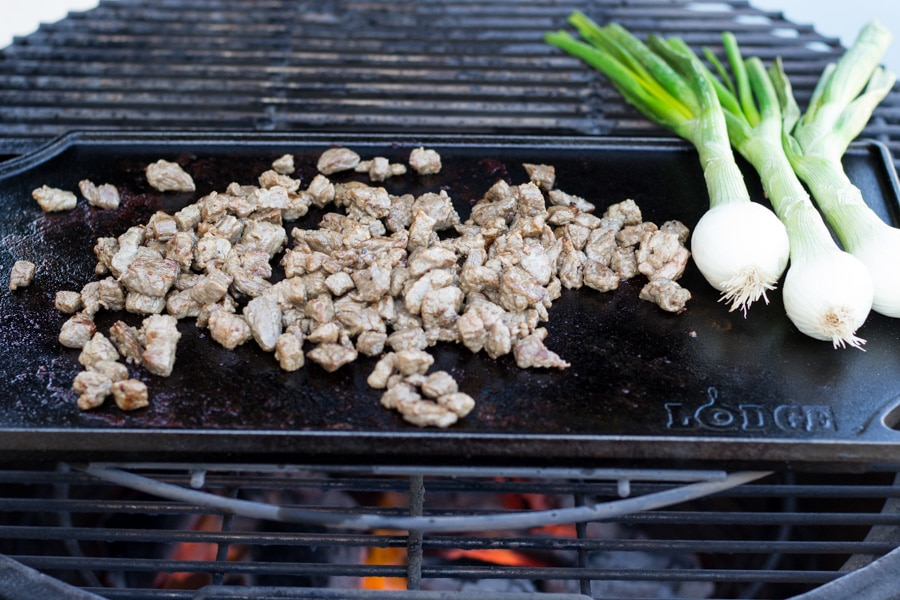 Cast iron flat top on an outdoor grill with steak cooking and onion bulbs.