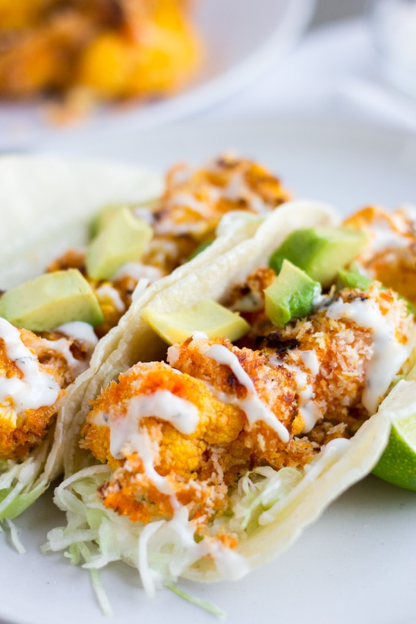 Two Buffalo Cauliflower tacos on a white plate with shredded cabbage on the bottom.