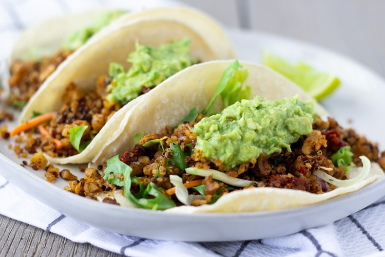 3 Vegan Chorizo tacos on a white plate topped with guacamole.