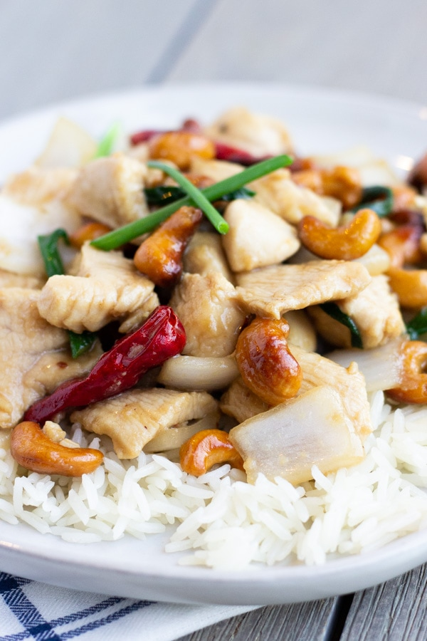 Cashew chicken over rice on a white plate.