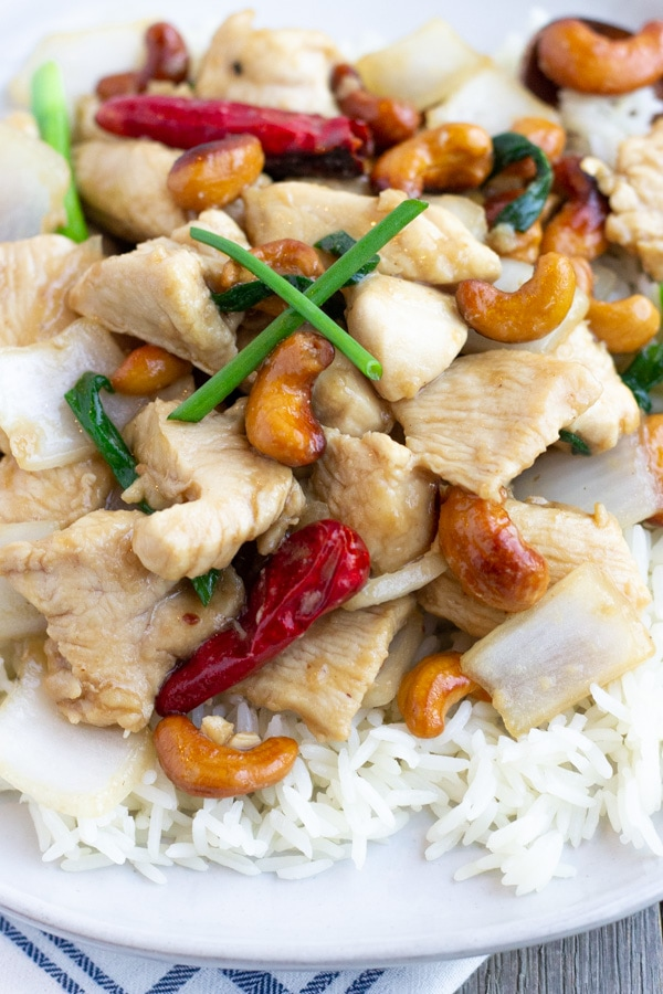 Up close view of cashew chicken over rice on a white plate.