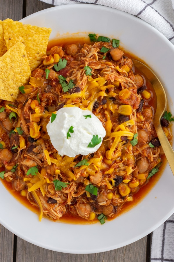 Chicken Taco Chili made in the Instant Pot or Crock Pot. Tender pieces of shredded chicken with corn, black beans, garbanzo beans, in a tomato base sauce.