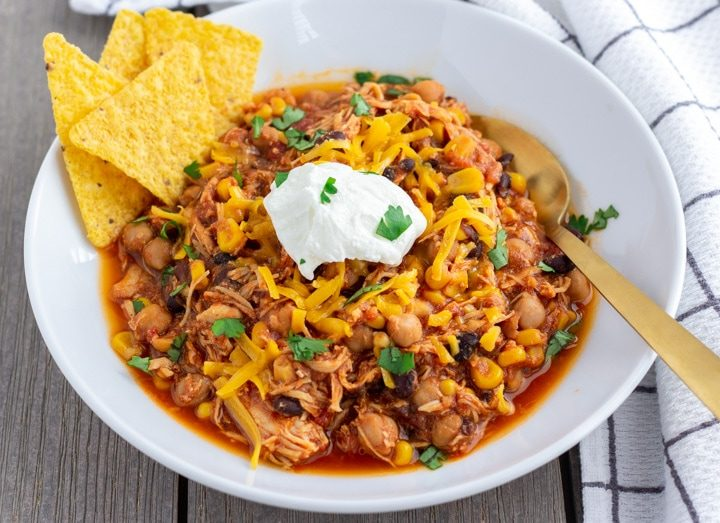 Landscape view of Chicken Taco Chili in a white bowl with a dollop of greek yogurt in the middle and tortilla chips on the side