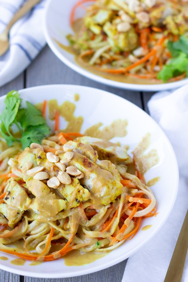 Two white bowls of spiralized zucchini and carrots topped with Thai chicken Satay and a creamy peanut sauce.