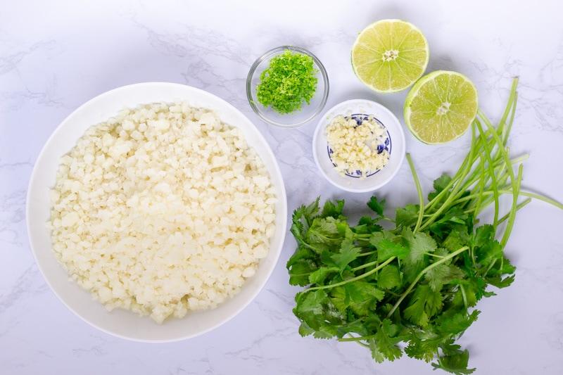 Spread of Ingredients, cauliflowe rice, cilantro, garlic, and lime cut in half