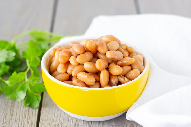 Cooked Peruvian beans in a small yellow bowl with cilantro on the side.