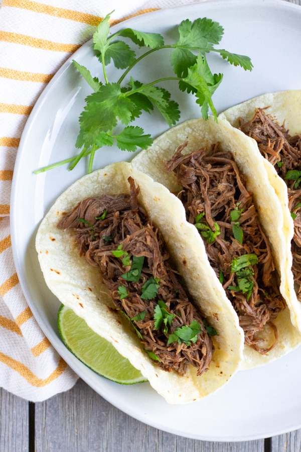 Three shredded beef tacos arranged on a white plate with a yellow striped napkin.