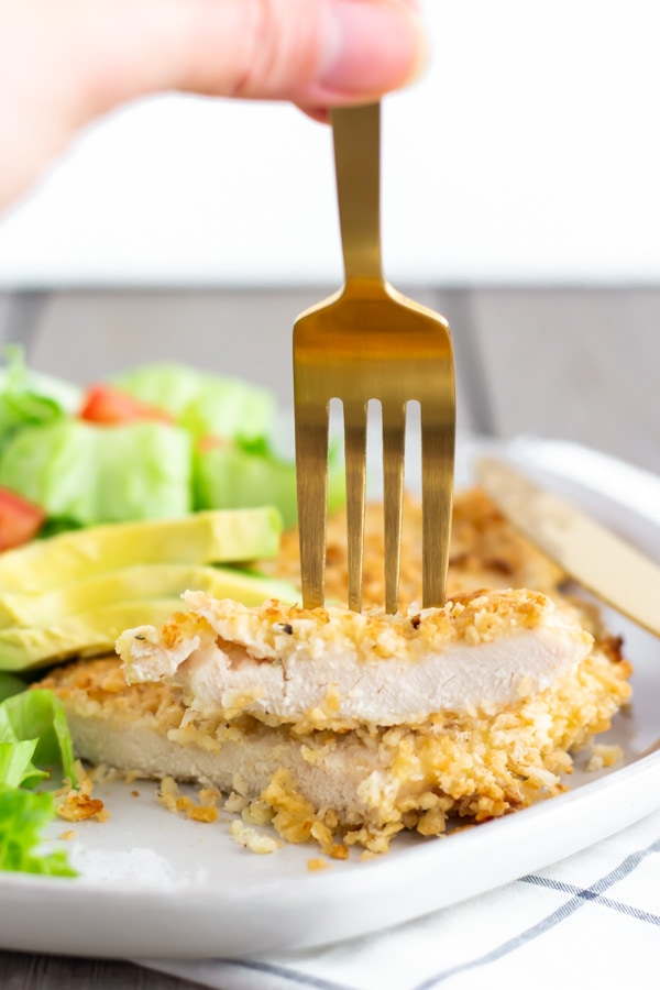 Chicken milanesa cut in half and stacked with a fork on top.