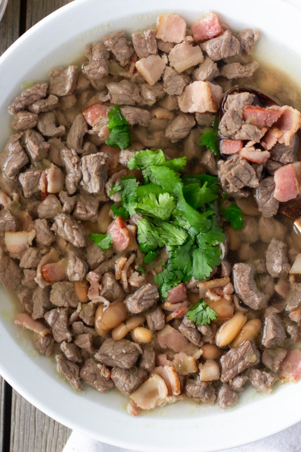 Carne en su jugo in a white bowl topped with cilantro.