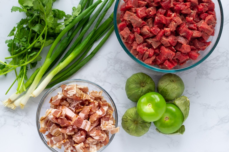 Ingredients for carne en su jugo- Beef, bacon, tomatillos, green onion, cilantro.