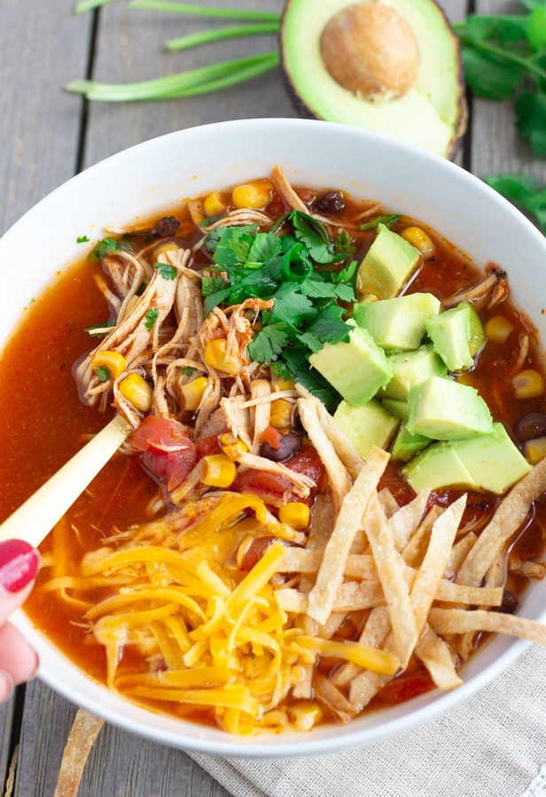 View of hand holding soup spoon in the chicken tortilla soup