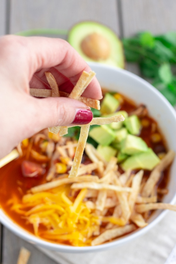 Hand shot of tortilla strips being sprinkled into chicken tortilla soup