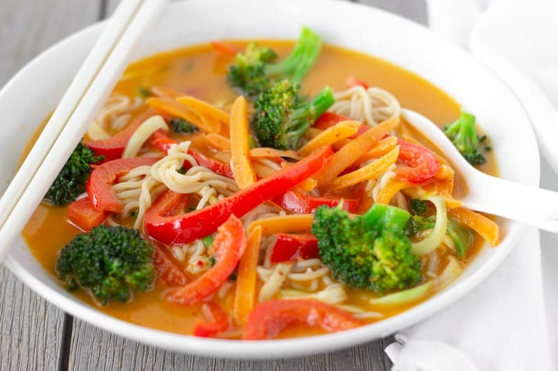 Thai red curry noodle bowl with chopsticks on the side and a white soup spoon.