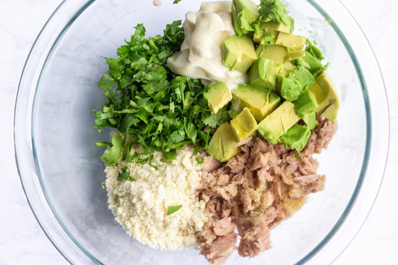 Glass bowl with ingredients for Avocado cilantro tuna cakes.