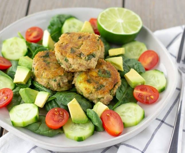 Avocado Cilantro Tuna Cakes on a bed of spinach with sliced cucumbers, tomatoes, and avocado.
