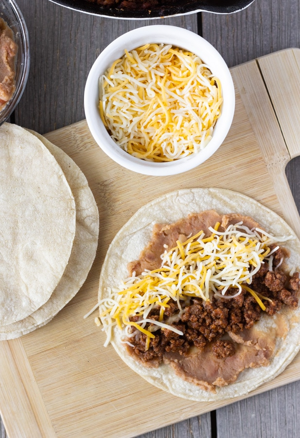 Tortilla on a cutting board layered with beans, ground beef, and shredded cheese.