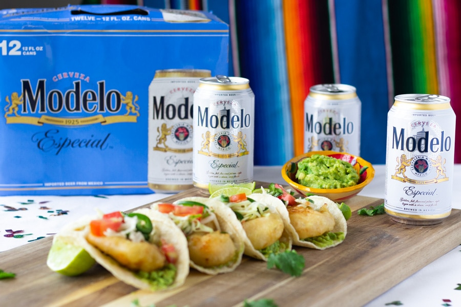 Modelo box displayed with cans surround beer battered shrimp tacos on a board.