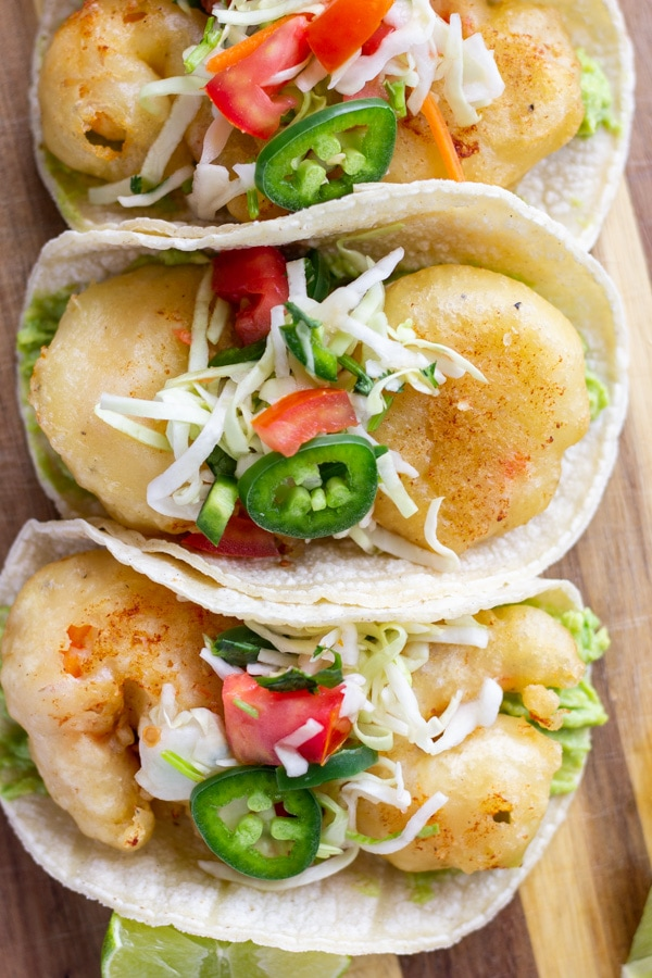 Beer Battered shrimp tacos topped with slaw and jalapenos on a wood board.