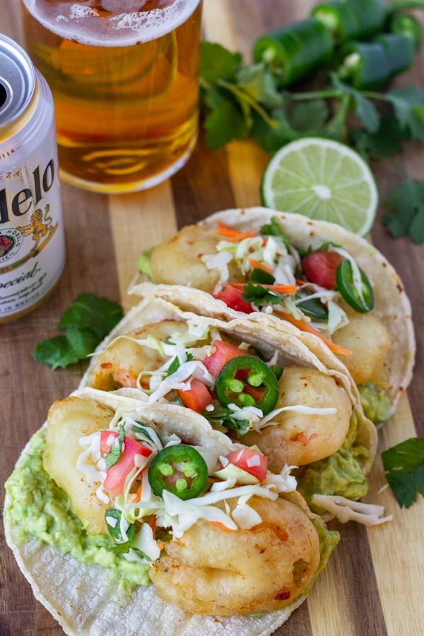 Beer Battered shrimp tacos topped with slaw and jalapenos on a wood board with a glass and can of Modelo on the side.