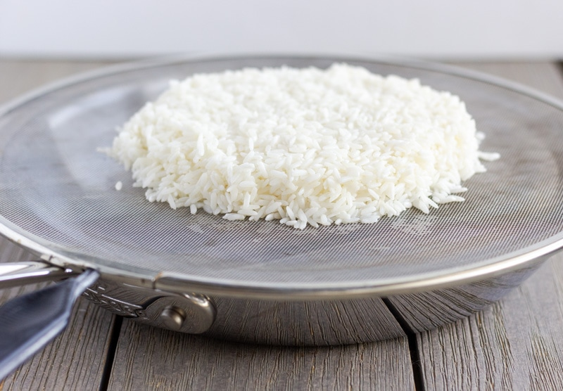 Saute pan with splatter guard as the cover, and a mound of sticky rice on top.